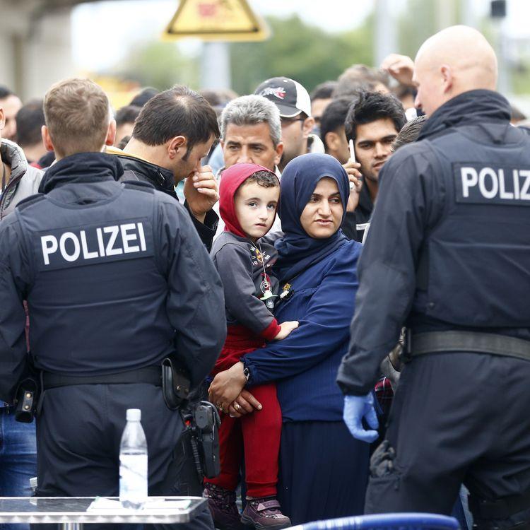 Des policiers surveillent des réfugiés descendant d'un train, à la gare de Freilassing (Allemagne), le 14 septembre 2015. (DOMINIC EBENBICHLER / REUTERS)