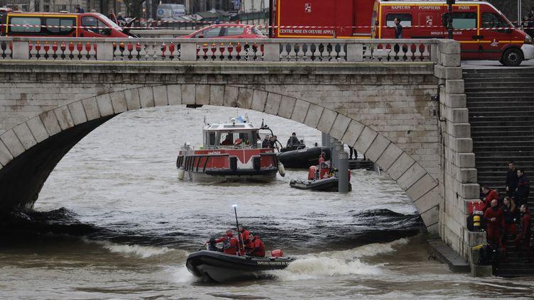 Les secours recherchent une policère de la bridage fluviale tombée dans la Seine, à Paris, vendredi 5 janvier. (THOMAS SAMSON / AFP)