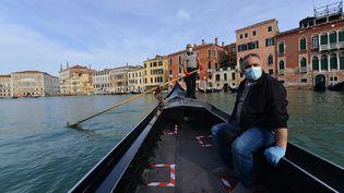 Un gondolier transporte son premier client, à la réouverture du service, lundi 18 mai 2020, à Venise (Italie). (ANDREA PATTARO / AFP)