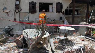 Un soldat israélien inspecte les ruines d'une maison détruite par une roquette du Hamas, le 22 juillet dans la vile de Yahud, en banlieue de Tel Aviv. (GIL COHEN MAGEN / AFP)