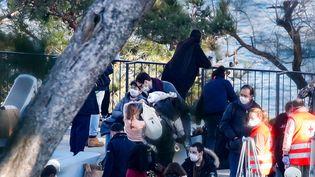 Des rapatriés français accueillis par des bénévoles de la Croix-Rouge, le 31 janvier 2020, à leur arrivée au centre de vacances de Carry-le-Rouet (Bouches-du-Rhône). (STR / AFP)