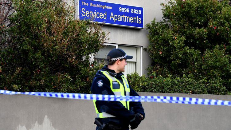 Un policier surveille l'entrée de l'immeuble situé dans la banlieue de Melbourne (Australie) où a eu lieu une prise d'otage, lundi 5 juin 2017. (STRINGER / REUTERS)
