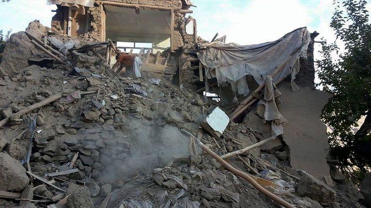 Un Afghan creuse dans les décombres d'un bâtiment endommagé après un puissant séisme dans le village de Raman Kheel, dans la vallée du Panshir, le 26 octobre 2015. (AFP)