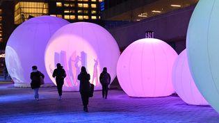 Des passants marchent à côté de lumières dans les rues de Montréal, le 14 décembre 2020. (ERIC THOMAS / AFP)