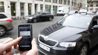 Un homme consulte l'application Uber sur son smartphone,qui permet de réserver un véhicule de tourisme avec chauffeur, à Paris, le 10 décembre 2014. (ELIOT BLONDET / AFP)