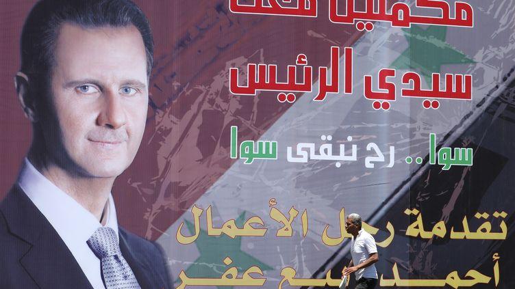 Un homme passe devant une affiche de campagne de Bachar Al-Assad pour les élections présidentielles syriennes, le 19 mai 2021 à Damas. (LOUAI BESHARA / AFP)