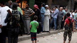 En Syrie, à Alep, icien juillet 2016, des habitants d'un quartier rebelle dans une file d'attente pour acheter du pain (ABDALRHMAN ISMAIL / REUTERS)