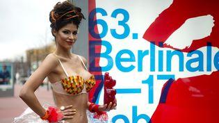 """Le top model allemand Micaela Schaefer pose avec un ours en relief autocollant sur le """"boulevard des Stars"""" devant l'affiche de la 63e Berlinale.  (ODD ANDERSEN / AFP)"""