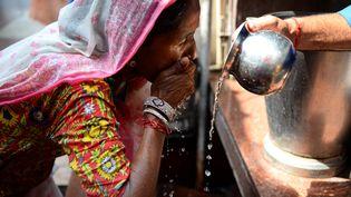 Un Indienne s'hydrate alors que la canicule frappe New Dehli en mai 2017 (SAJJAD HUSSAIN / AFP)