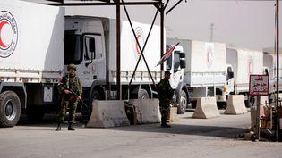 Des camions du Croissant rouge syrien, transportant de l'aide humanitaire, attendent à un checkpoint près de Damas, le 5 mars 2018. (OMAR SANADIKI / REUTERS)