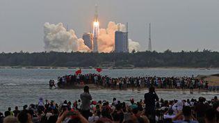 Des curieux assistent au lancement du premier module de la station spatiale chinoise,le 29 avril 2021 à Wenchang (Chine). (KOKI KATAOKA / YOMIURI / AFP)