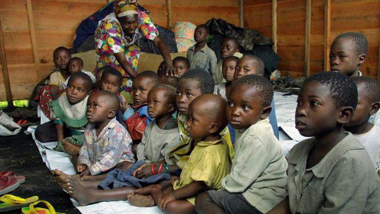 Des enfants congolais séparés de leurs parents dans un centre de la Croix-Rouge à Goma, après l'éruption du volcan Nyiragongo, le 22 janvier 2002. De nombreux orphelins en provenance du Nord-Kivu en guerre ont été transférés dans les orphelinats de Kinshasa. (Photo AFP/Pedro Ugarte)