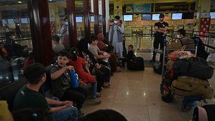 Des passagers s'apprêtent à embarquer dans un vol de Qatar Airways à l'aéroport de Kaboul, en Afghanistan, le 9 septembre 2021. (WAKIL KOHSAR / AFP)