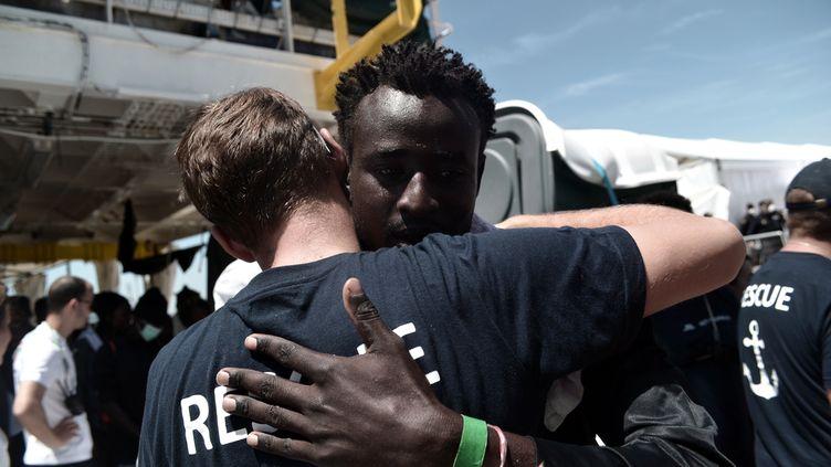 """Un homme sauvé par le bateau humanitaire """"l'Aquarius"""" enlace un membre de l'équipage, après avoir débarqué dans le port de Valence, en Espagne, le 17 juin 2018. (KARPOV / SOS MEDITERRANEE / AFP)"""