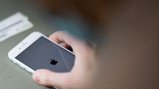 Une personne manipulant un téléphone Apple. (LOIC VENANCE / AFP)