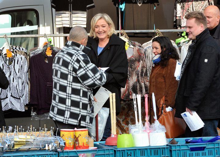 La présidente du FN, Marine Le Pen, et le responsable du FN dans le Pas-de-Calais, Laurent Brice, discutent avec des passants sur le marché d'Oignies, le 30 octobre 2012. (PHILIPPE HUGUEN / AFP)
