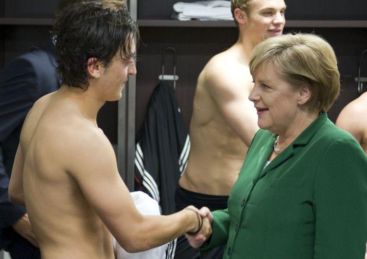 Angela Merkel salue le milieu de terrain Mesut Özil dans les vestiaires après un match Allemagne-Turquie (3-0), le 8 octobre 2010. (GUIDO BERGMANN / REUTERS)