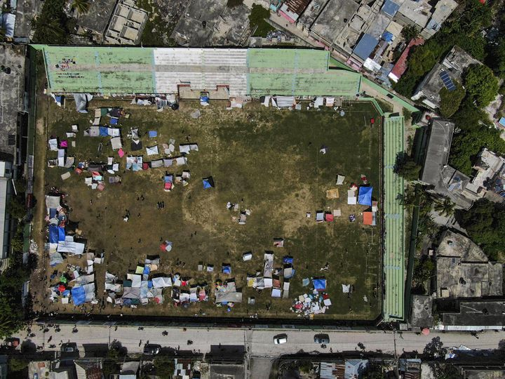 Des abris de fortune érigés sur le terrain de football des Cayes (Haïti),lundi 16 août 2021, après le tremblement de terre qui a ravagé le sud du pays. (FERNANDO LLANO / AP / SIPA)