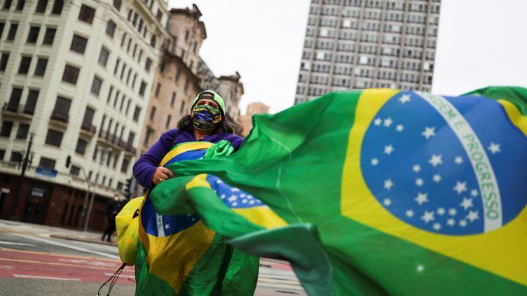 Un manifestant portant un masque de protection et un drapeau du Brésil, lors d'une manifestation en soutien au président Jair Bolsonaro, le 14 juin à Sao Paulo. (AMANDA PEROBELLI / X06790)