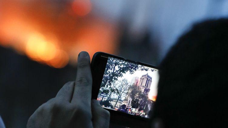 Un homme photographie la cathédrale Notre-Dame de Paris en feu, le 15 avril 2019. (LAURE BOYER / HANS LUCAS)