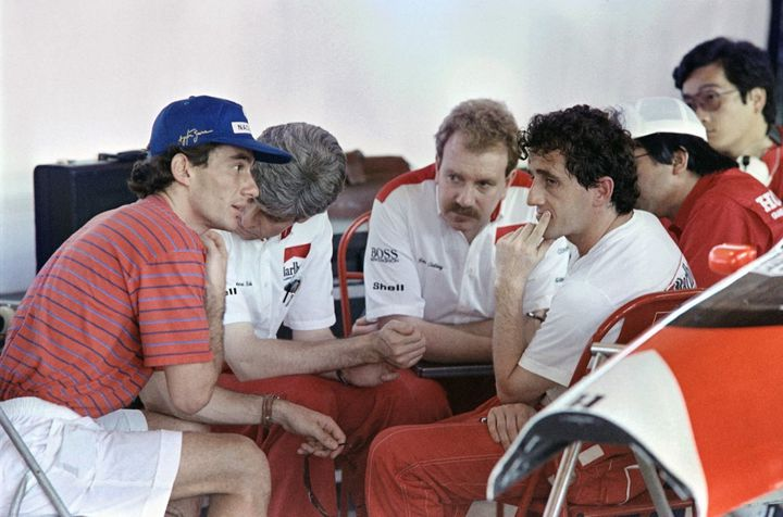 Le Brésilien Ayrton Senna et le Français Alain Prost dans les stands de l'écurie McLaren, le 18 mars 1989, avant le Grand Prix du Brésil. (ANDREW MURRAY / AFP)