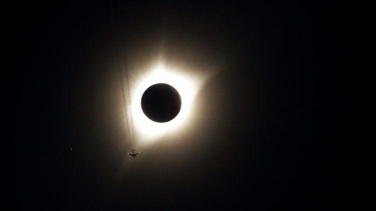 Un avion passe devant l'éclipse, au-dessus de Guernsey, dans le Wyoming (Etats-Unis), le 21 août 2017. (RICK WILKING / REUTERS)
