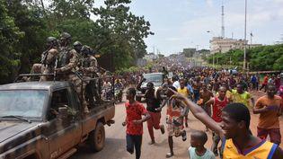 La foule en liesse accompagne des soldats qui viennent de prendre le pouvoir le 5 septembre 2021 à Conakry, capitale de la Guinée. (CELLOU BINANI / AFP)