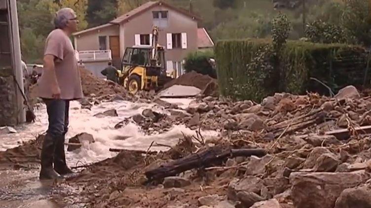 Un habitant deSaint-Martin-de-Valamas (Ardèche) dans une rue du vilage dévastée par les inondations provoquées par les violents orages, le 13 octobre 2014. ( FRANCE 2)