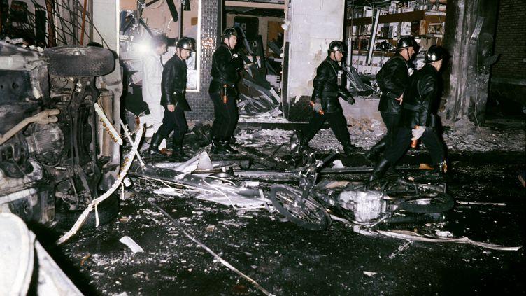 Des secouristes traversent les décombres après l'explosion, le 3 octobre 1980 à Paris. (GEORGES GOBET / AFP)