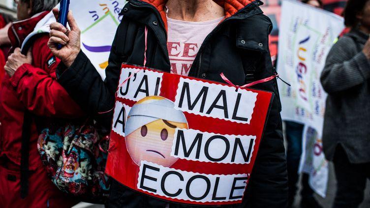 """Une femme arbore une pancarte """"J'ai mal à mon école"""", à Paris, le 19 mars 2019. (BENJAMIN MENGELLE / HANS LUCAS / AFP)"""