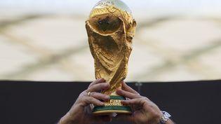 Le Brésilien Rivelino brandit le trophée de la Coupe du monde, lors d'une présentation à Manaus (Brésil), le 19 mai 2014. (BRUNO KELLY / REUTERS)