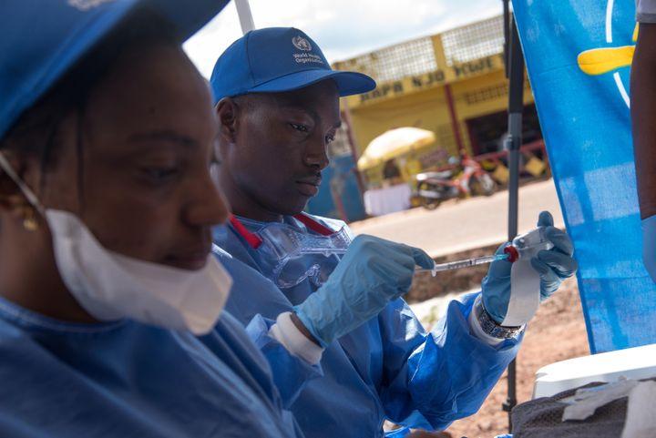 Dessoignants travaillant avec l'Organisation mondiale de la santé (OMS) se préparent à administrer des vaccins dans toute la ville de Mbandaka, le 21 mai 2018, lors du lancement de la campagne de vaccination contre Ebola. (JUNIOR D. KANNAH / AFP)