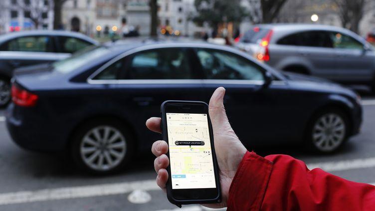 Un client consulte sur son téléphone son application Uber à Washington le 25 mars 2015. (ANDREW CABALLERO-REYNOLDS / AFP)