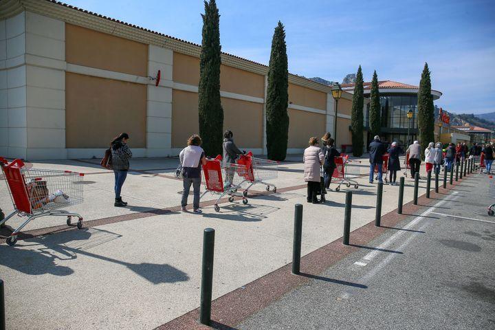 Des clients font la queue devant un supermarché, à Valence (Drôme), le 27 mars 2020. (NICOLAS GUYONNET / HANS LUCAS / AFP)