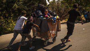 Un groupe de migrants mineurs et leur charriot sur une route de Mytilène sur l'île de Lesbos, le 11 septembre 2020. (ANGELOS TZORTZINIS / AFP)