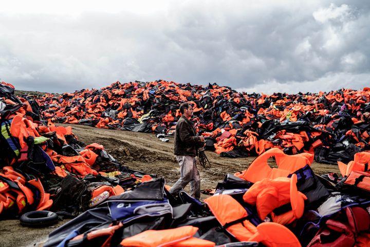 Un homme marche au milieu de gilets de sauvetage laissés par des migrants, après leur traversée de la mer Egée et leur arrivée sur l'île grecque de Lesbos (Grèce), le 27 novembre 2015. (HALIT ONUR SANDAL / NURPHOTO)
