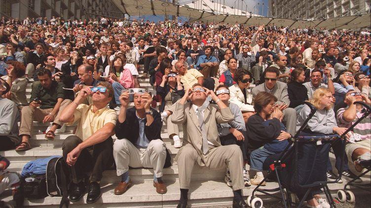 Des Français observent l'éclipse totale de soleil du 11 août 1999 sur le parvis de La Défense, à Paris.. (MAXPPP)