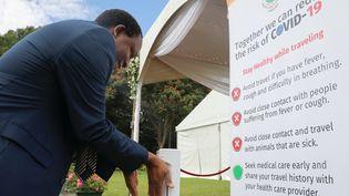 A Harare, capitale du Zimbabwe, un homme se désinfecte les mains grâce à un distributeur automatique. Les consignes sont exclusivement en anglais. Photo réalisée le 19 mars 2020. (PHILIMON BULAWAYO / X02381)