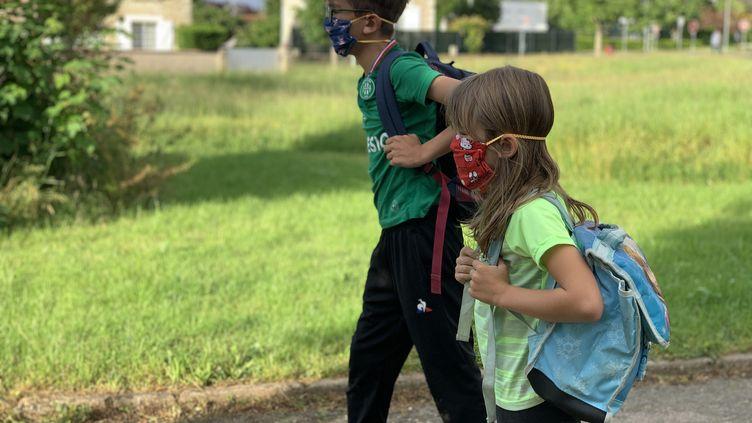 À Buxerolles (Vienne), durant le confinement, des enfants équipés de masques en tissu pour se rendre à l'école, le 3 mai 2020. (VINCENT HULIN / FRANCE-BLEU POITOU)