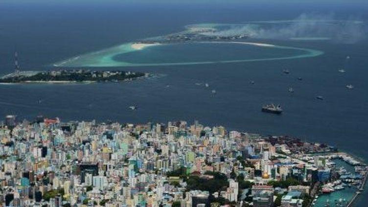 Maldives, septembre 2013. Au marge de l'île capitale de Malé, de la fumée s'échappe de l'île poubelle de Thilafushi. (ROBERTO SCHMIDT / AFP)