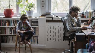 Un homme et son fils dans un salon, le 2 avril 2020. (CELINE GAILLE / HANS LUCAS / AFP)