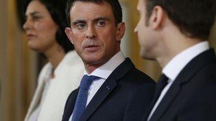 Manuel Valls aux côtés de Myriam El Khomri et Emmanuel Macron, à Paris,le 11 mars 2016. (THOMAS SAMSON / AFP)