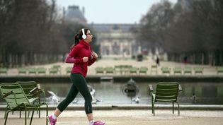 Une femme fait son jogging dans le jardin des Tuileries, à Paris, en mars 2015. (LOIC VENANCE / AFP)