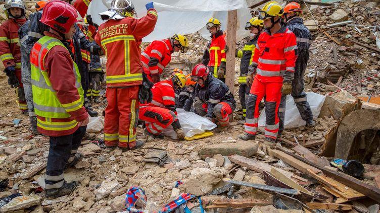 """Des pompiers recouvrent un corps découvert dans les décombres, le 6 novembre 2018, au lendemain de l'effondrement dedeux immeubles à Marseille, et le jour où une """"soirée chocolat"""" a réuni plusieurs élus municipaux. (BMPM/SM / AFP)"""