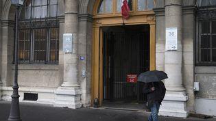 Un homme marche devant le 36 quai des Orfèvres, siège de la police judiciaire parisienne, le 25 avril 2014. (JOEL SAGET / AFP)