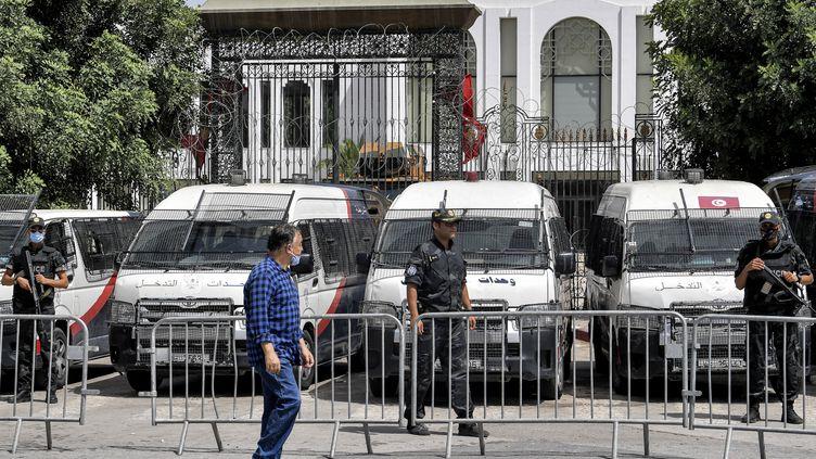 Un homme passe devant des membres des forces de sécurité tunisiennes qui montent la garde devant le siège du parlement au Bardo à Tunis, le 31 juillet 2021. (FETHI BELAID / AFP)