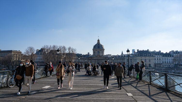Des Parisiens profitent du soleil sur le Pont des Arts, lors du premier week-end du reconfinement, le 20 mars 2021. (SANDRINE MARTY / HANS LUCAS / AFP)
