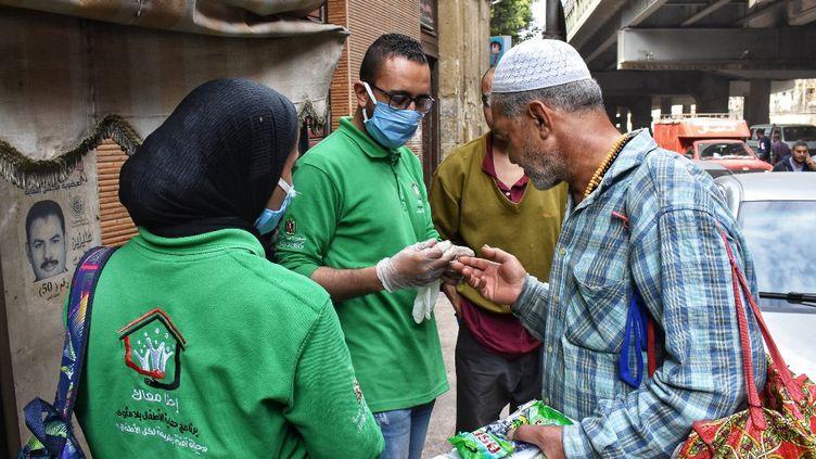 Des membres d'une association distribue, le 9 avril, du désinfectant à un SDF, en Egypte, l'un des pays africains le plus touché par le coronavirus. (ZIAD AHMED / NURPHOTO / AFP)