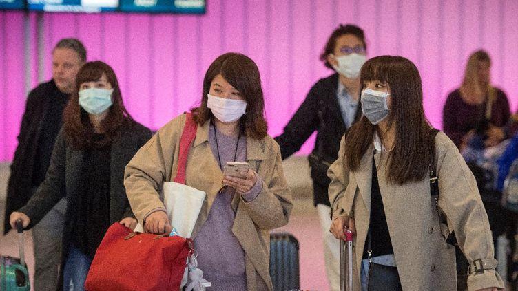 Des passagers portent des masques pour se protéger du coronavirus 2019-nCoV, à l'aéroport de Los Angeles (Californie, Etats-Unis), le 22 janvier 2020. (Mark RALSTON / AFP)