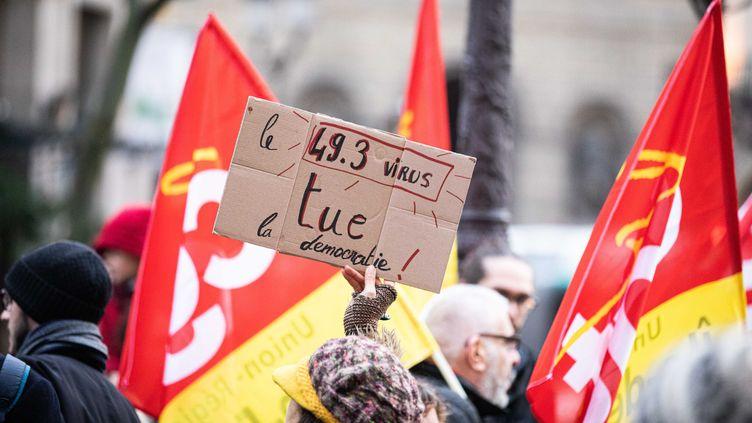 Une manifestante brandit une pancarte contre le recours à l'article 49.3 pour adopter la réforme des retraites, le 1er mars 2020, à Paris. (MAXPPP)